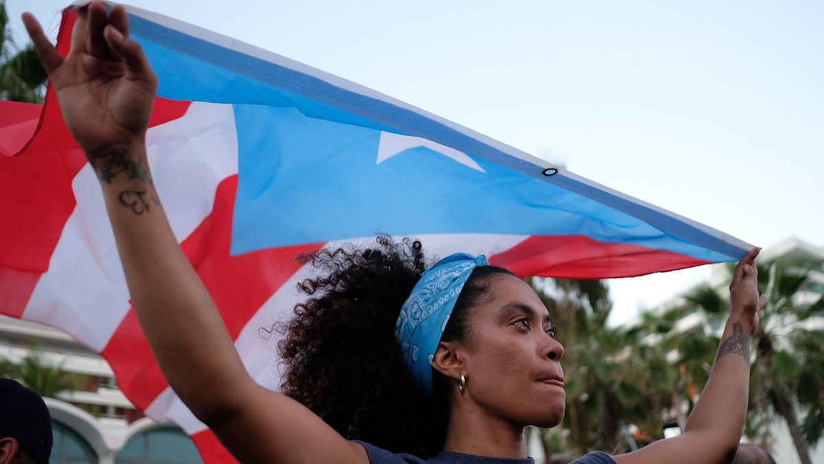 This May 2, 2018, file photo shows a person marching to protest pension cuts, school closures and slow hurricane recovery efforts in the El Condado tourist zone in San Juan, Puerto Rico.