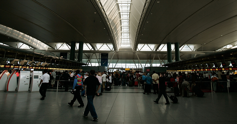 FILE - Travelers and airport employees walk through New York City's John F. Kennedy Airport in this file photo. A security breach at JFK on Feb. 20, 2017, resulted in 11 passengers getting through security without being screened, officials are reporting.
