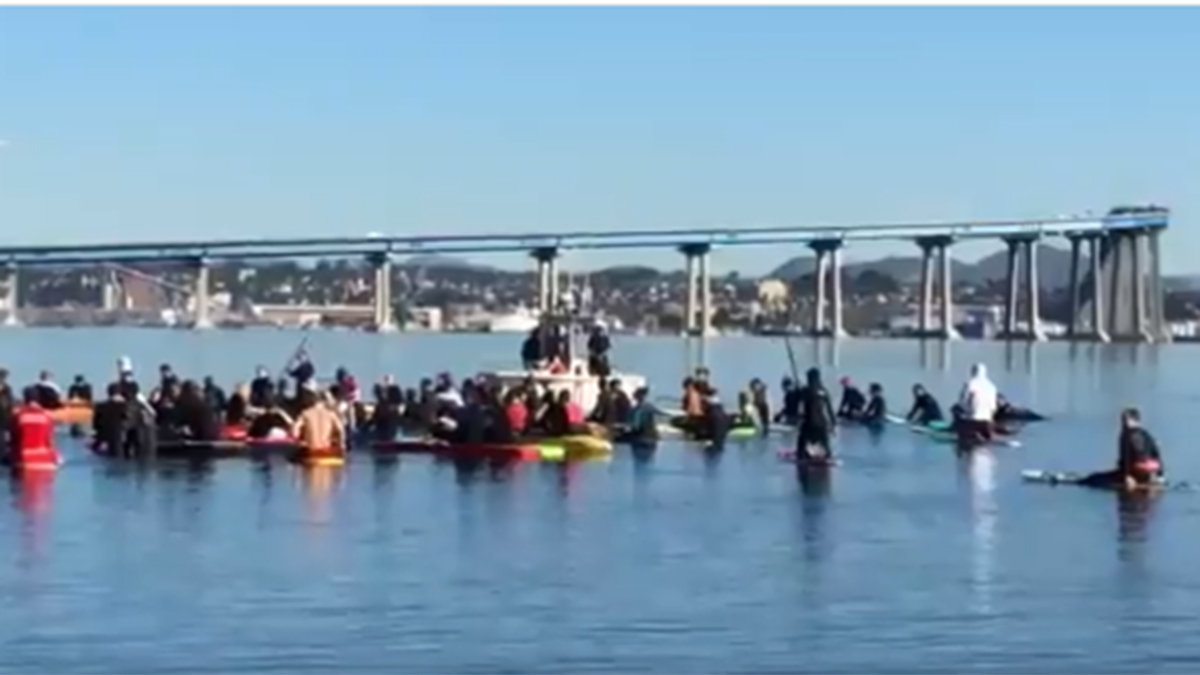 A group paddled out to the water off North Beach in Coronado on Dec. 8, 2018, to remember Justin Meek.