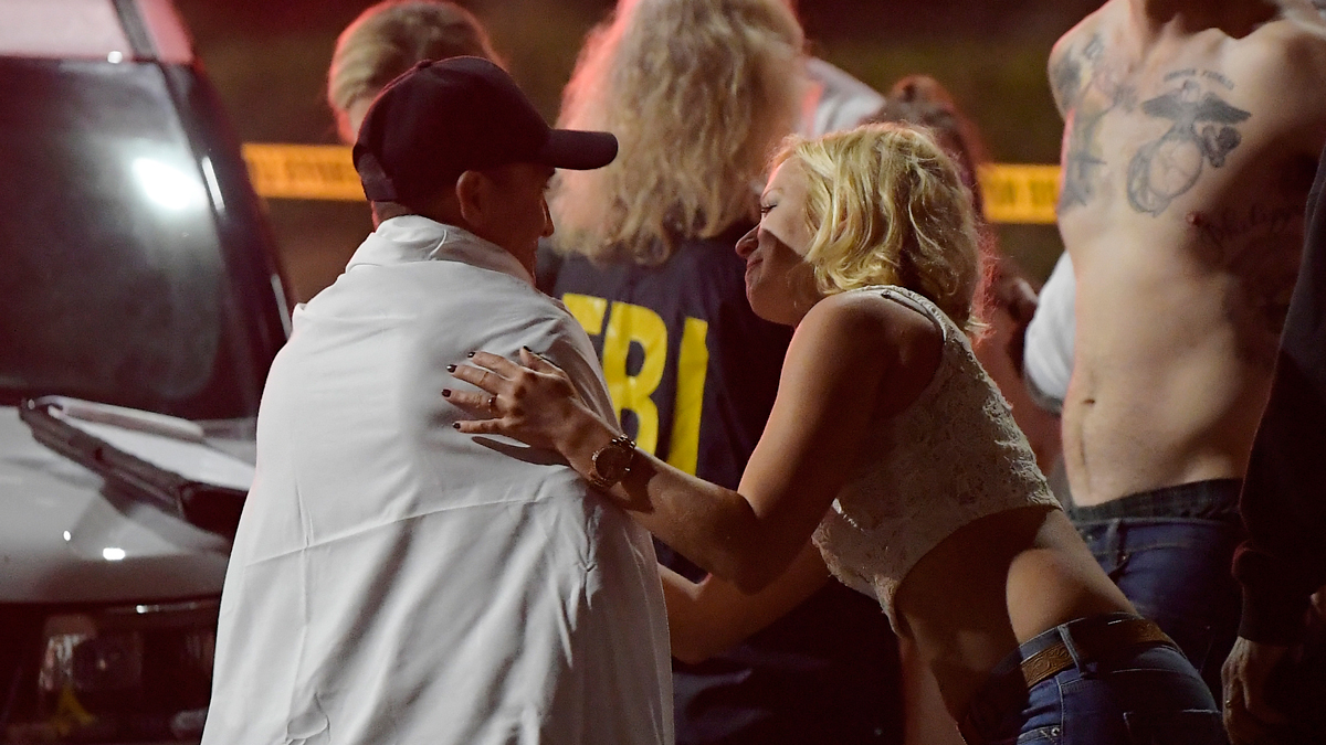 People comfort each other as they sit near the scene Thursday, Nov. 8, 2018, in Thousand Oaks, Calif. where a gunman opened fire Wednesday inside a country dance bar crowded with hundreds of people on