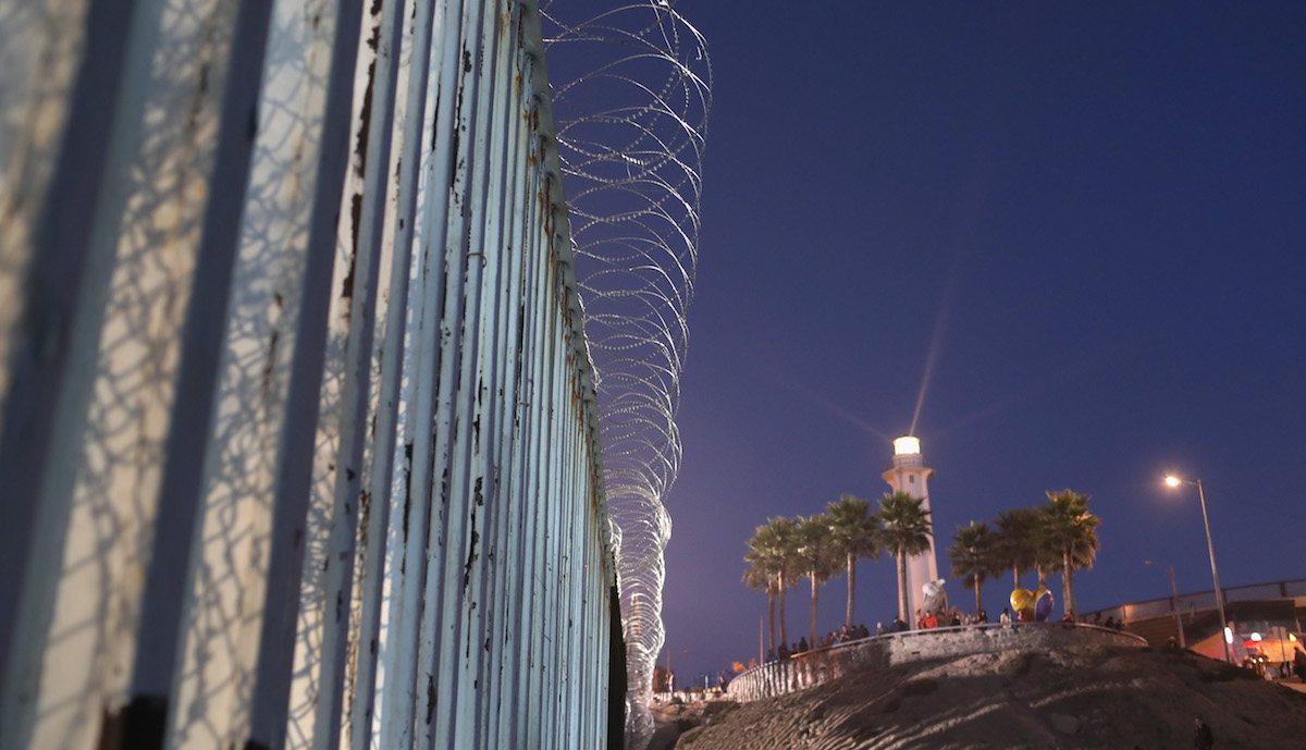 A Mexican lighthouse shines above the U.S.-Mexico border fence on Nov. 16, 2018, in San Diego, California, as seen from Tijuana, Mexico. U.S. border agencies continued to fortify the fence with razor wire as members of the migrant caravan arrived to Tijuana across the border from San Diego.