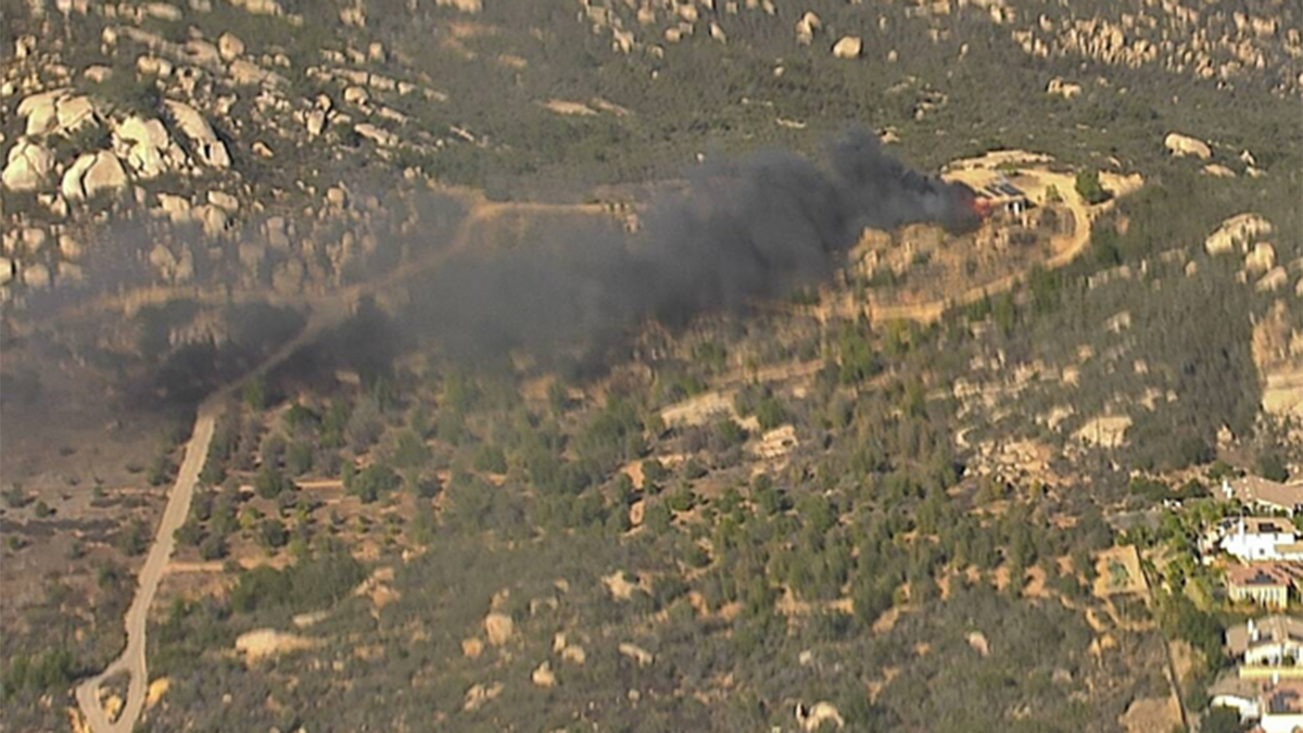 A fire produces black smoke on the camera facing north from Mount Woodson.