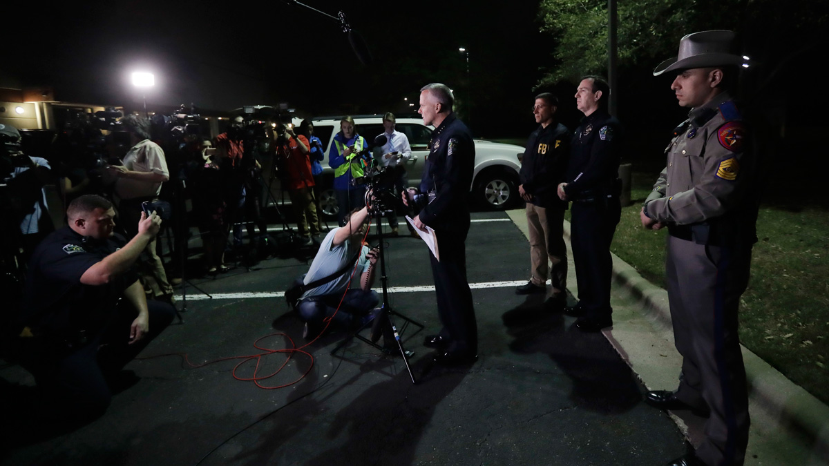Interim Austin police Chief Brian Manley, center, talks to the media after an explosion, Monday, March 19, 2018, in Austin, Texas. The area around the explosion site has been blocked off and authorities are interviewing neighbors and searching for possible witnesses.