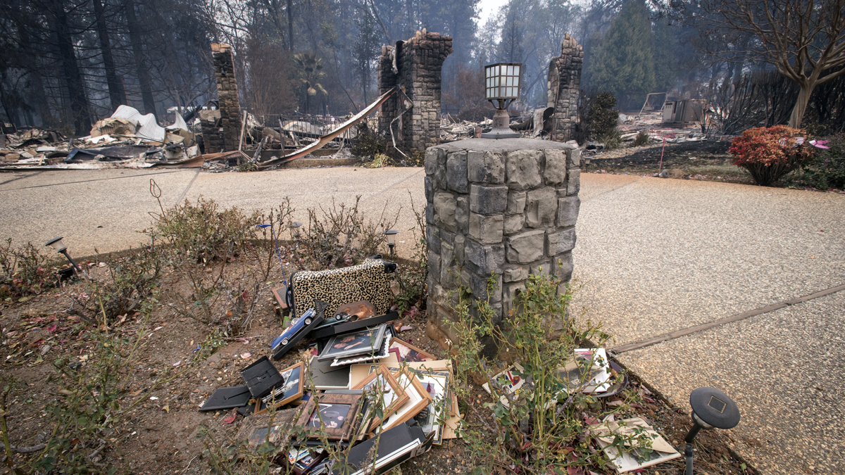 Photographs lie on the ground in front of a burned-out home during the Camp Fire in Paradise, California, U.S., on Tuesday, Nov. 13, 2018. The Camp Fire north of Sacramento has now killed at least 48 people.