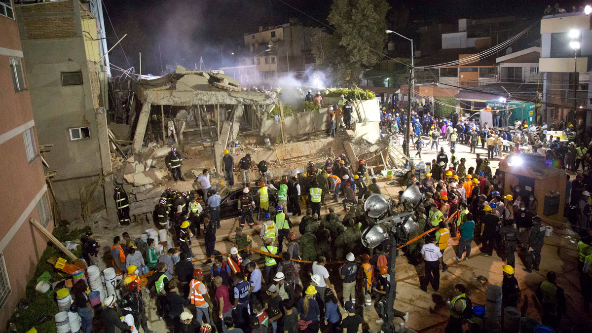 Volunteers and rescue workers search for children trapped inside at the collapsed Enrique Rebsamen school in Mexico City, Tuesday, Sept. 19, 2017.