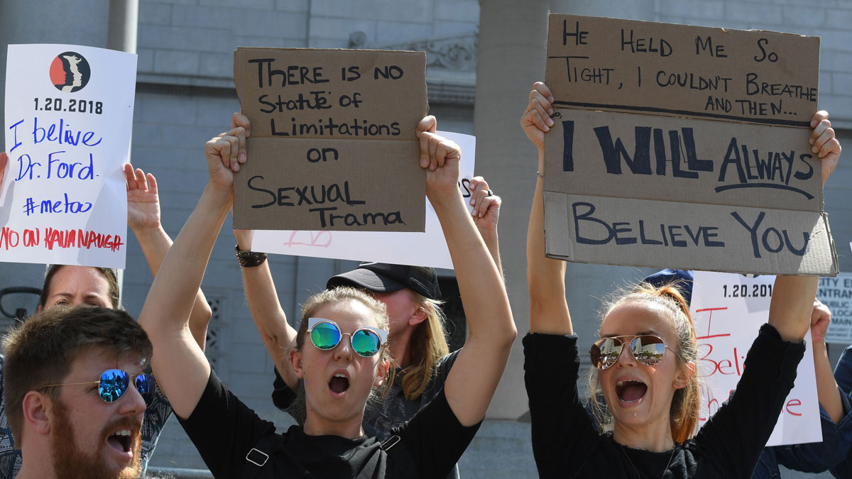 Demonstrators hold anti-Kavanaugh hold posters outside City Hall in Los Angeles on Sept. 28, 2018. -