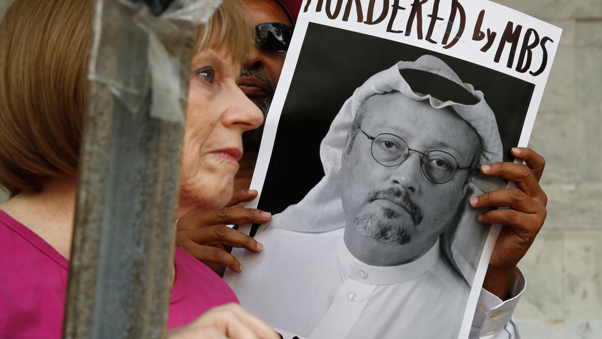 FILE - In this Oct. 10, 2018, file photo, people hold signs during a protest at the Embassy of Saudi Arabia about the disappearance of Saudi journalist Jamal Khashoggi, in Washington.