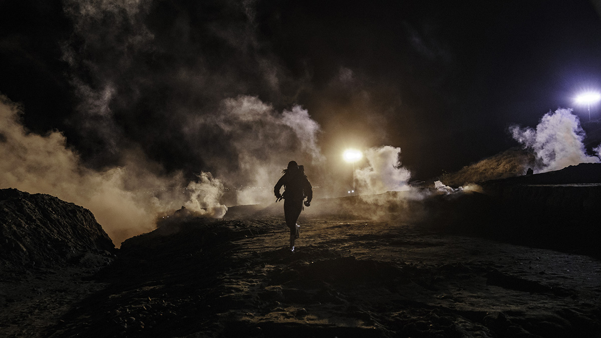 Migrants run as tear gas is thrown by U.S. Border Protection officers to the Mexican side of the border fence after they climbed the fence to get to San Diego, Calif., from Tijuana, Mexico, Tuesday, Jan. 1, 2019. Discouraged by the long wait to apply for asylum through official ports of entry, many migrants from recent caravans are choosing to cross the U.S. border wall and hand themselves in to border patrol agents.