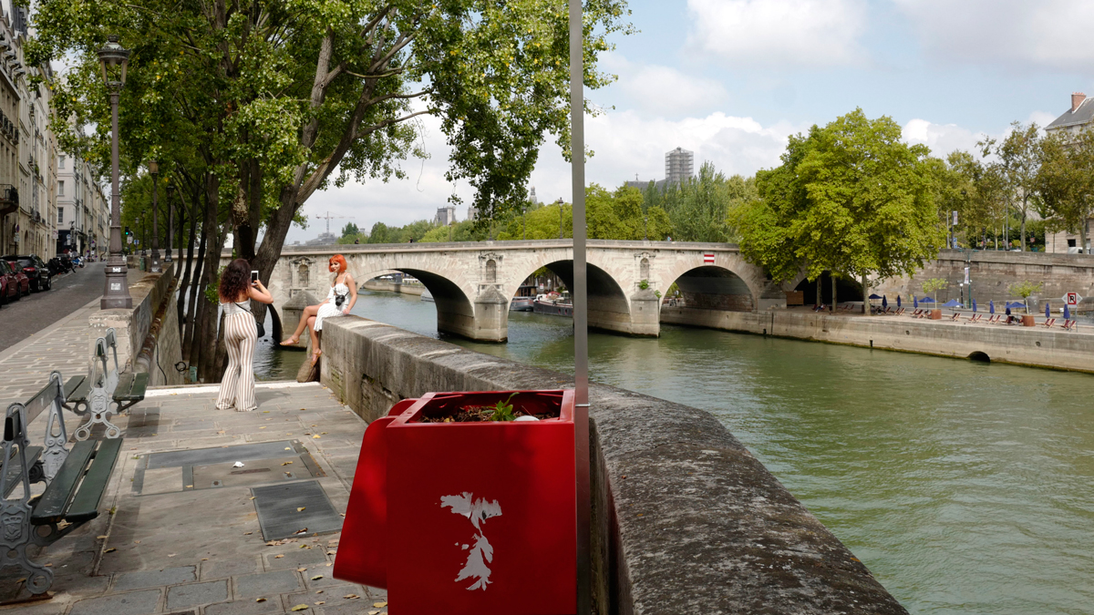 Women take photos on the Seine river banks on the Ile de la Cite where an urinal has been installed, Tuesday, Aug.14, 2018 in Paris. Some residents have written to the town hall to demand its removal from this touristic area not far away form Notre Dame Catheral.