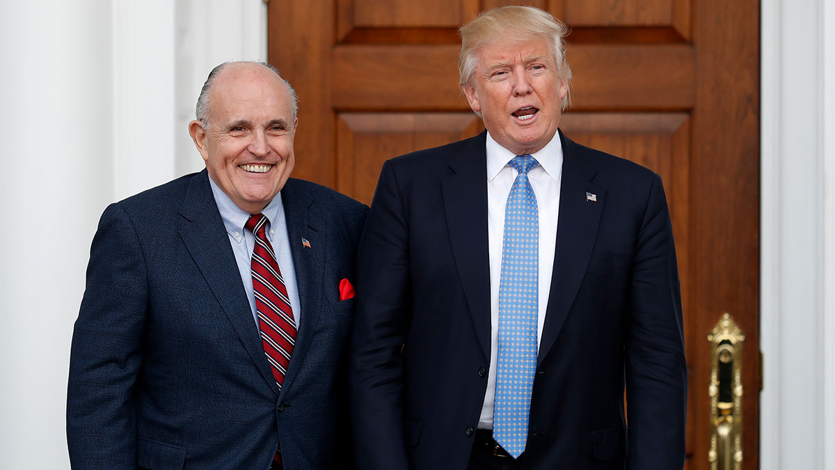 File - President-elect Donald Trump calls out to media as he and former New York Mayor Rudy Giuliani pose for photographs as Giuliani arrives at the Trump National Golf Club Bedminster clubhouse, Sunday, Nov. 20, 2016, in Bedminster, N.J..