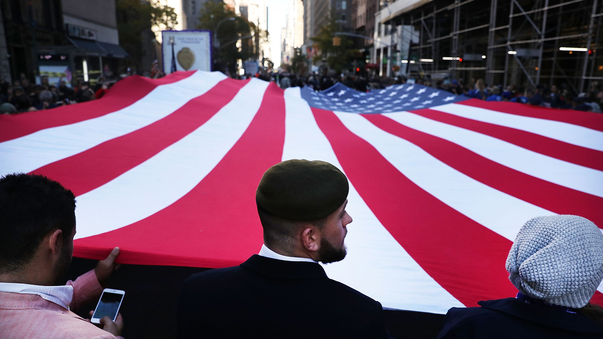 In this Nov. 11, 2016, file photo, veterans and others carry a large American Flag while marching in the nation's largest Veterans Day Parade in New York City.