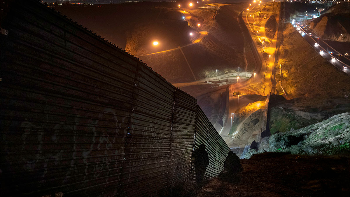 Migrants looks for a place to jump the border fence to get into the U.S. side to San Diego, Calif., from Tijuana, Mexico, Saturday, Dec. 29, 2018.